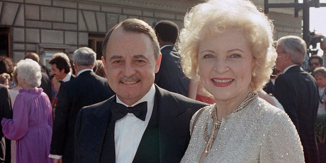 """FILE- This Sept. 22, 1985, file photo shows John Hillerman, left, and Betty White, right, arriving at Emmy Awards in Pasadena, Calif. A spokeswoman for the family of Hillerman says the co-star of TV's """"Magnum, P.I."""" has died. Hillerman was 84. Spokeswoman Lori De Waal said Hillerman died Thursday at his home in Houston. She said the cause of death has yet to be determined. (AP Photo/LIU, File)"""