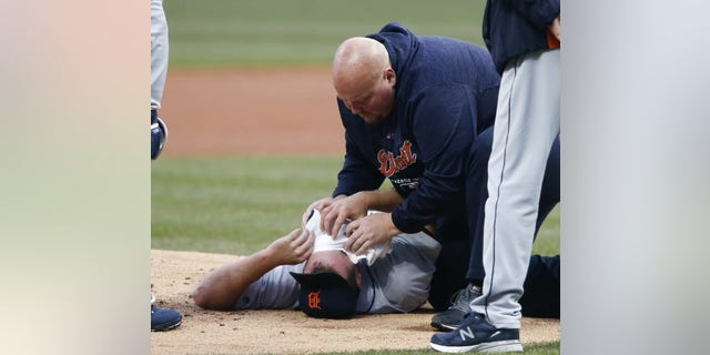 Detroit Tigers starting pitcher Jordan Zimmermann is tended to by head athletic trainer Doug Teter after getting hit by a ball off the bat of Cleveland Indians' Jason Kipnis during the first inning in a baseball game Wednesday, April 11, 2018, in Cleveland.
