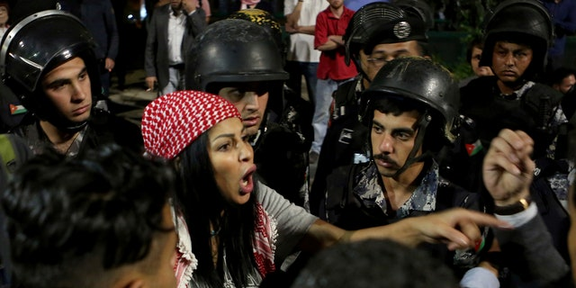 Jordanian protesters argue with members of the gendarmerie and security forces during a demonstration outside the Prime Minister's office in the capital Amman early Monday, June 4, 2018.