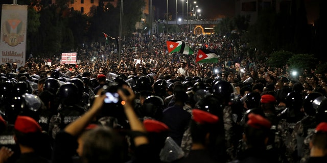 Jordanian protesters shout slogans and raise a national flag during a demonstration outside the Prime Minister's office in the capital Amman early Monday, June 4, 2018.