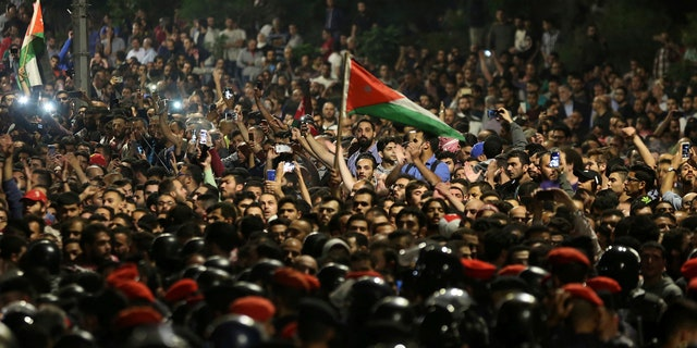 Jordanian protesters shout slogans and raise a national flag during a demonstration outside the Prime Minister's office in the capital Amman late early Monday, June 4, 2018.