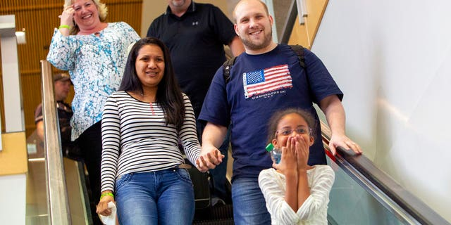 Josh Holt returned with wife, Thamara Caleno, left, and daughter, Marian, bottom, to a crowd of friends and family in Salt Lake City.