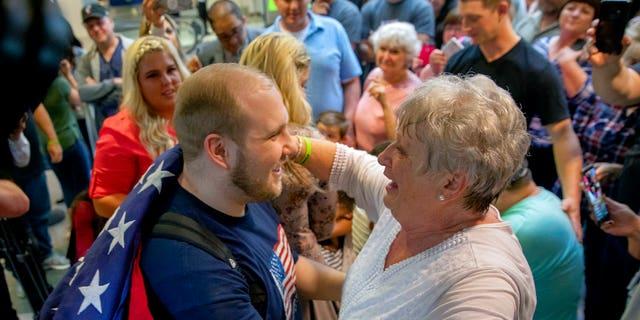 Holt's grandmother, Linda Holt, draped an American flag on Josh Holt's shoulder upon his return to Salt Lake City.