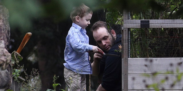Joshua Boyle and son Jonah play in the garden at his parents house in Smiths Falls, Ont., on Saturday, Oct. 14, 2017. A couple held hostage for five years by a Taliban-linked network and forced to raise three children while in captivity were initially targeted for ransom because of the impending birth of their first child, the Canadian man at the heart of the case speculated Saturday. Boyle said he and his wife Caitlan Coleman heard at least half a dozen reasons why they had been snatched from a village in Afghanistan and held against their will by the Haqqani network over the years they were imprisoned. (Lars Hagberg/The Canadian Press via AP)