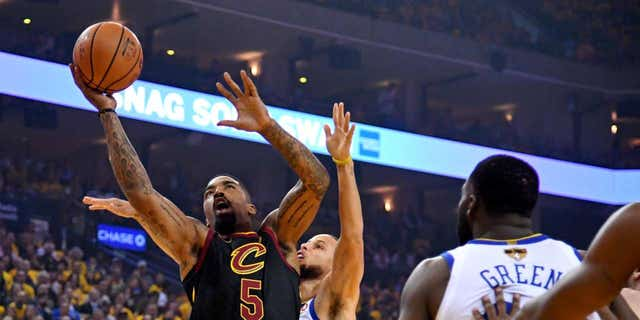 Cleveland's J.R. Smith, 5, handles the ball, surrounded by Golden State's Stephen Curry and Draymond Green.