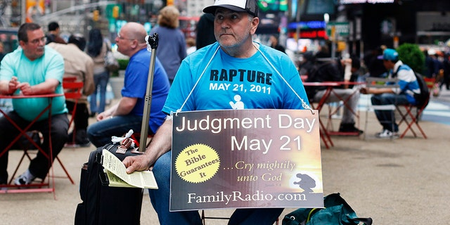 Man sits in New York's Times Square in 2011 warning about the end of the world, as predicted by Evangelist preacher Harold Camping