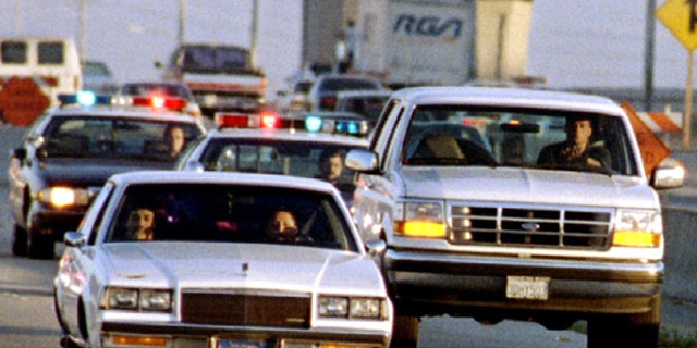 A Ford Bronco carrying O.J. Simpson (hidden in rear seat) is reportedly driven by Simpson's former teammate Al Cowlings, chased by dozens of police cars during an hour long pursuit through Los Angeles area freeways, June 17.