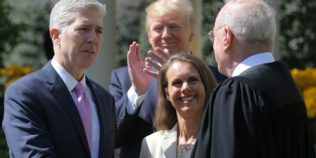FILE: April 10, 2017: Judge Neil Gorsuch shakes hands with Supreme Court Associate Justice Anthony Kennedy after being sworn into the Supreme Court. He is accompanied by wife Louise Gorsuch and President Trump in the White House Rose Garden, Washington, D.C.