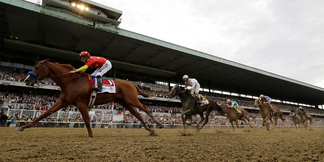 Justify (1), with jockey Mike Smith up, crosses the finish line to win the 150th running of the Belmont Stakes horse race and the Triple Crown on Saturday in Elmont, N.Y.