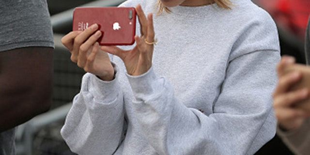 Hailey Baldwin snapped taking footage of her fiance while in front of Buckingham Palace.