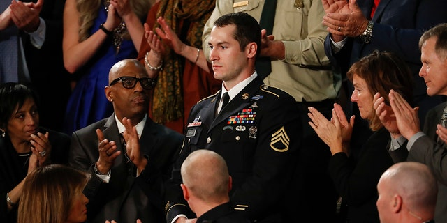 Army Staff Sgt. Justin Peck, center, stands as he's introduced by President Donald Trump during the State of the Union address to a joint session of Congress on Capitol Hill in Washington.
