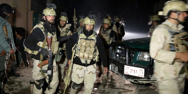 Jan. 17, 2014: Afghan security forces leave the site of a suicide attack in Kabul, Afghanistan.