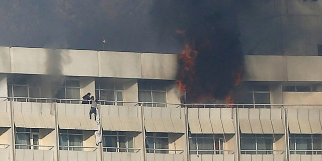A man tries to escape from a balcony at Kabul's Intercontinental Hotel during an attack by gunmen in Kabul, Afghanistan January 21, 2018