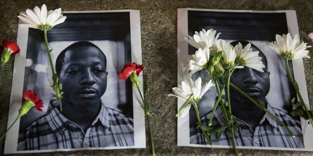 Flowers rest on top of pictures of Kalief Browder in New York. Browder had been held there for three years without being convicted of a crime.