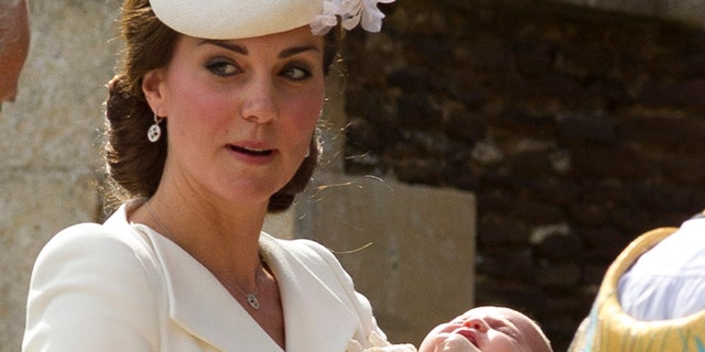 Kate Middleton carries Princess Charlotte after taking her out of a pram as they arrive for Charlotte's Christening at St. Mary Magdalene Church in Sandringham, England.