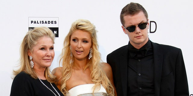 May 20, 2010. Paris Hilton (C), her mother Kathy (L) and her brother Barron Nicholas Hilton arrive for the amfAR';s Cinema Against AIDS 2010 event in Antibes during the 63rd Cannes Film Festival.