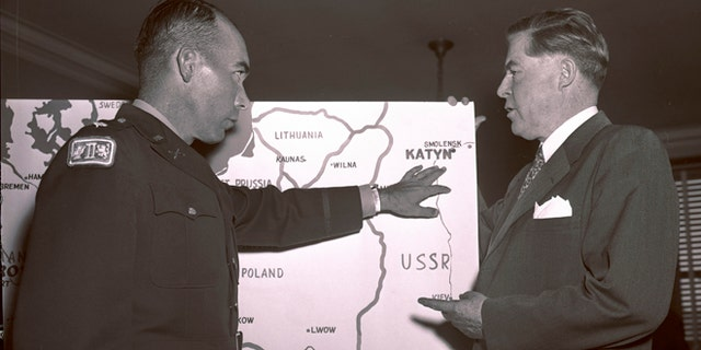 In this Oct. 11, 1951 file photo, Lt. Col. Donald B. Stewart, left, locates the site of a mass grave near near Smolensk, Russia, to Rep. Ray Madden, D-Ind., during a special House Committee hearing in Washington. Stewart and Lt. Col. John H. Van Vliet Jr., were among a group of British and American prisoners forced by the Germans to see a horrifying site, a mass grave where murdered Polish officers were buried, near Smolensk.