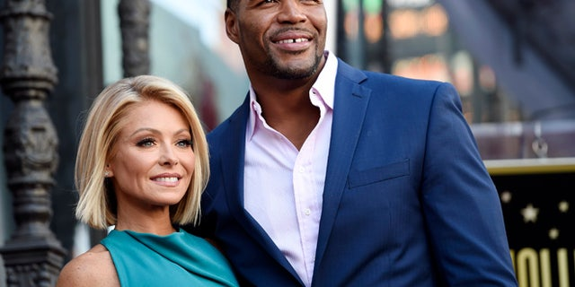"""In this Oct. 12, 2015 file photo, Kelly Ripa, left, poses with Michael Strahan, her co-host on the daily television talk show """"LIVE! with Kelly and Michael,"""" during a ceremony honoring Ripa with a star on the Hollywood Walk of Fame in Los Angeles."""