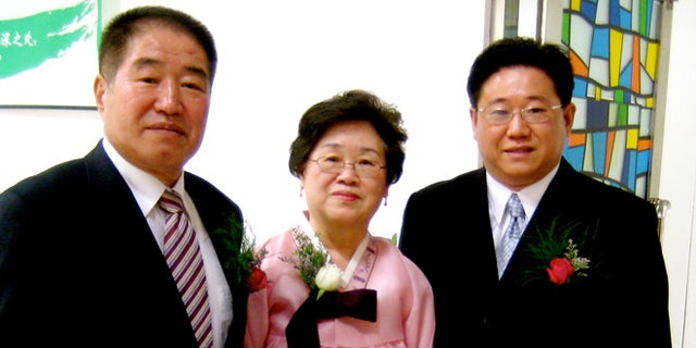 In this undated photo provided by the family of Kenneth Bae, Kenneth Bae, right, poses for a photo with his parents, Sung Seo Bae, left, and Myunghee Bae, center. Bae, a 45-year-old tour operator and Christian missionary was arrested last November while leading a group of tourists in the northeastern region of Rason in North Korea and has been detained for the past 11 months. Bae's family said on Thursday, Oct. 10, 2013, that Bae's mother, Myunghee Bae, is being allowed to visit him.