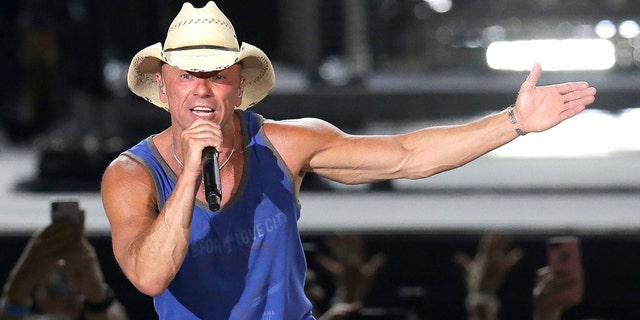 """In this June 23, 2018 file photo, Kenny Chesney performs during the Trip Around the Sun Tour in Phoenix. After Hurricane Irma decimated the U.S. Virgin Islands last year, country superstar Kenny Chesney started writing songs and organizing relief efforts. Chesney is donating proceeds from the sale of his new album, """"Songs for the Saints,"""" to a foundation he set up to support recovery on the islands."""