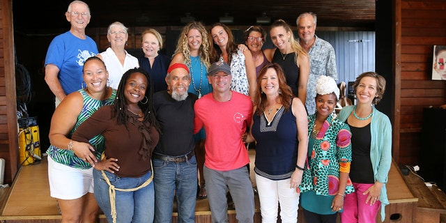 In this Feb. 28, 2018 photo provided by Jill Trunnell, country singer Kenny Chesney, foreground center, poses with residents, background from left, Jim Furneaux, Carol Furneaux, Glenda Werbel, Angela Warren, Jenna Fox, Jude Woodcock, Jillian Grossman and Bill Stelzer, and foreground from left, Audrey Penn, Ingrid Smith, Eddie Bruce, Chesney, Kim Wild, Jeune Provost and Lauren Magnie at St. John School of the Arts in St. John, U.S. Virgin Islands.