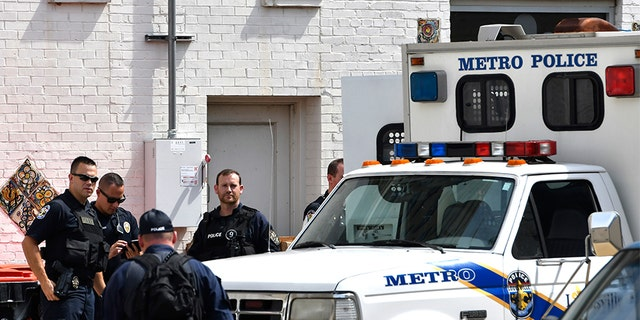 July 26, 2018: Officers with the Louisville Metro Police wait to load members of the Occupy ICE movement into a van at the rear of the Heyburn building.