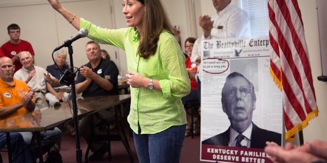 July 30, 2014: U.S. Senate candidate and Kentucky Secretary of State Alison Lundergan Grimes (D-KY), speaks to supporters in Hawesville, Ky., as a poster of her rival Senate Minority Leader Mitch McConnell of Ky., serves as a backdrop. (AP)