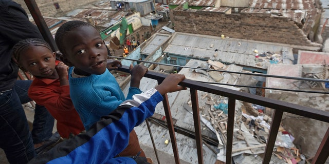 Child residents of a neighboring building look out over their balcony at the scene of a five-storey collapsed building in the Huruma neighborhood of Nairobi, Kenya, June 3, 2018.