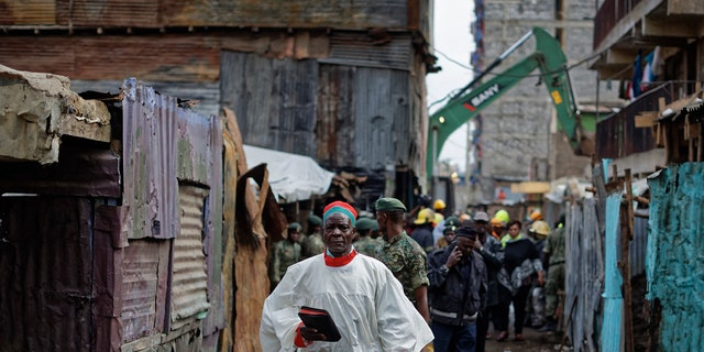 A priest holding a bible walks past the scene of a five-storey collapsed building in the Huruma neighborhood of Nairobi, Kenya, June 3, 2018.