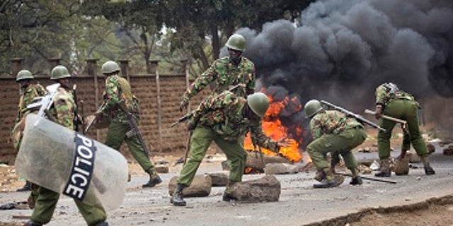 Kenyan security forces remove stones from a street blocked by supporters of Kenyan opposition leader and presidential candidate Ralia Odinga who demonstrated in the Mathare area of Nairobi Wednesday, Aug. 9, 2017.