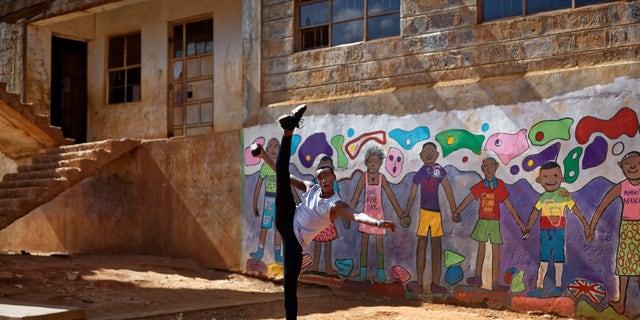 Kenyan ballet dancer Joel Kioko, 16, strikes a pose as a joke as he walks through the courtyard of a school where he was teaching young dancers in Nairobi, Kenya.