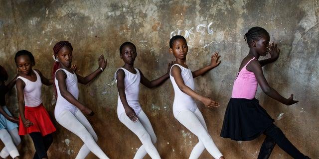 Young ballerinas practice under the instruction of Kenyan ballet dancer Joel Kioko, 16.