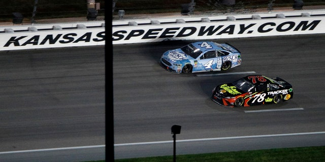Kevin Harvick (4) passes Martin Truex Jr. (78) with a lap to go to win the NASCAR Cup Series auto race at Kansas Speedway on Saturday, May 12, 2018, in Kansas City, Kan.