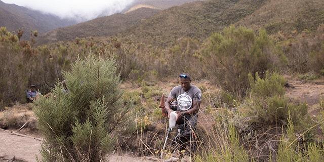 Cpl. Kionte Storey, 29, fixes his prosthetic while climbing Mount Kilimanjaro in Tanzania.