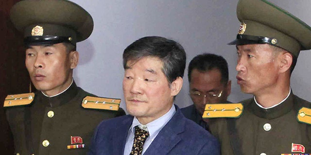 A photo of Kim Dong Chul being escorted by North Korean guards.