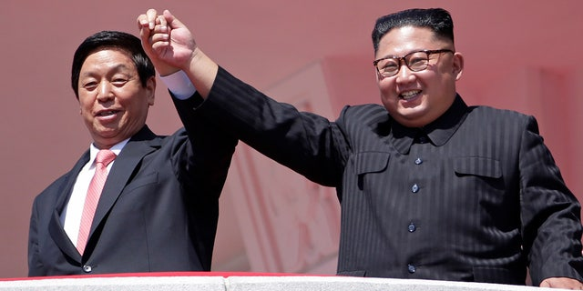 North Korean leader Kim Jong Un, right, raises hands with China's third-highest ranking official, Li Zhanshu, during a parade for the 70th anniversary of North Korea's founding day in Pyongyang, North Korea, Sept. 9, 2018.