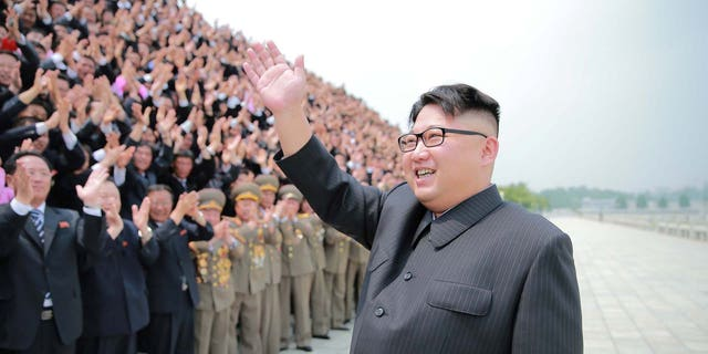 North Korean leader Kim Jong Un waves as he participates in a photo session with officials.