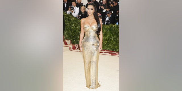 Kim Kardashian dons a golden Versace gown with embellished crosses at the gala carpet.