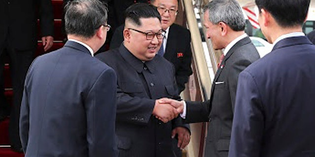 North Korean leader Kim Jong Un, left, is greeted by Singapore Minister for Foreign Affairs Dr. Vivian Balakrishnan, at the Changi International Airport, June 10, 2018.