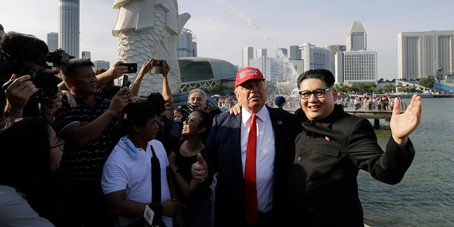 Howard X, along with Trump impersonator Dennis Alan, posed for photos with tourists in Merlion Park following X's alleged detainment.