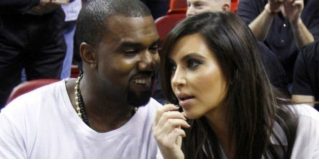 Dec. 6, 2012: Kanye West, left, talks to his girlfriend Kim Kardashian before an NBA basketball game between the Miami Heat and the New York Knicks in Miami.