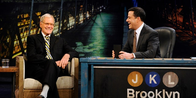 """In this Oct. 31, 2012 photo released by ABC, host Jimmy Kimmel, right, speaks with guest David Letterman during """"Jimmy Kimmel Live,"""" in the Brooklyn borough of New York. New York's late-night TV hosts were back in swing, though, with all resuming regular production Wednesday. Kimmel, who usually broadcasts from Los Angeles, is doing a week of shows in Brooklyn."""