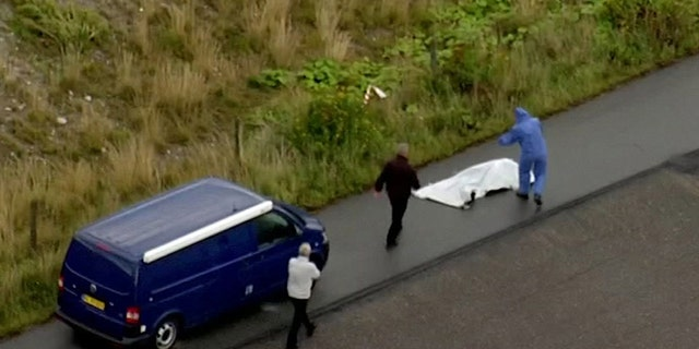 In this image taken from video on Monday Aug. 21, 2017, shows police forensic investigators as they prepare to move a headless body of a woman that was found near Amager Denmark in the Baltic Sea.
