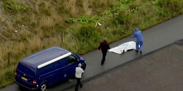 Police forensic investigators prepare to move the headless body of Kim Wall.