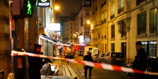 A police officer cordons off the area after a knife attack in central Paris, Saturday May 12, 2018.
