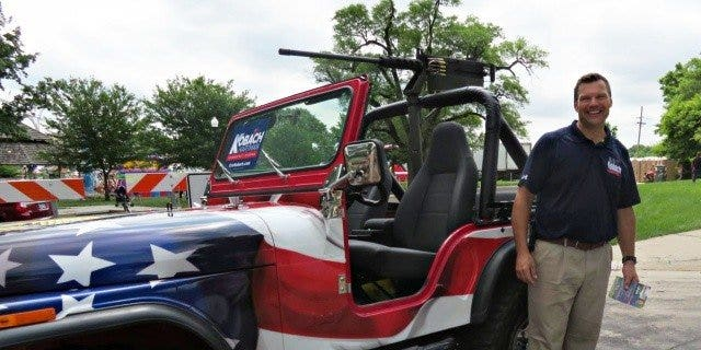 Republican Kansas governor hopeful Kris Kobach pictured with the jeep mounted with a replica of a gun that sparked the outrage.