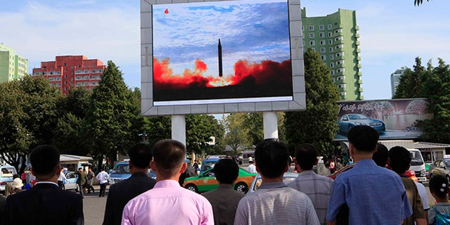 Photo released Saturday shows people watching a launching of a Hwasong-12 strategic ballistic rocket aired on a public TV screen at the Pyongyang Train Station in Pyongyang, North Korea.