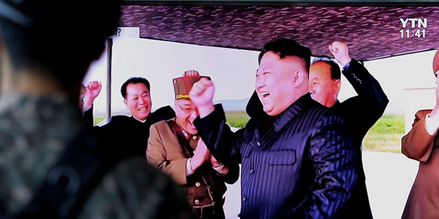 North Korean leader Kim Jong Un, center, celebrates the test launch Friday of an intermediate range Hwasong-12 missile at an undisclosed location in North Korea