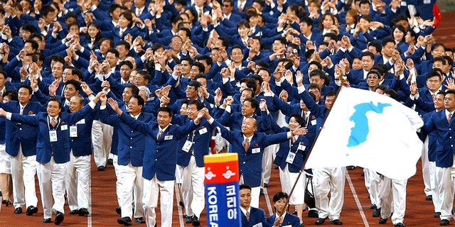 Sept. 29, 2002: Athletes from North and South Korea march together, led by a unification flag, during an opening ceremony for the 14th Asian Games in Busan, South Korea.