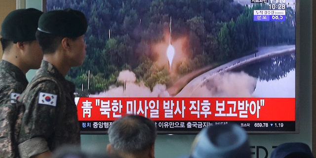 "Army soldiers walk by a TV news program showing a file image of a missile being test-launched by North Korea at the Seoul Railway Station in Seoul, South Korea, Tuesday, July 4, 2017. North Korea on Tuesday launched yet another ballistic missile in the direction of Japan, South Korean officials said, part of a string of recent test-firings as the North works to build a nuclear-tipped missile that could reach the United States. The signs read ""The presidential Blue House was briefed immediately after the North Korean missile was fired."" (AP Photo/Ahn Young-joon)"